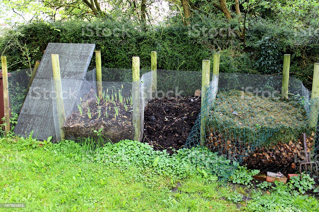 Image of wire recycling compost heaps in shady garden corner stock photo
