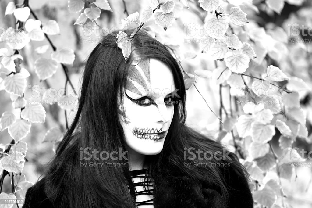 B&W image of woman wearing Halloween makeup outside. stock photo
