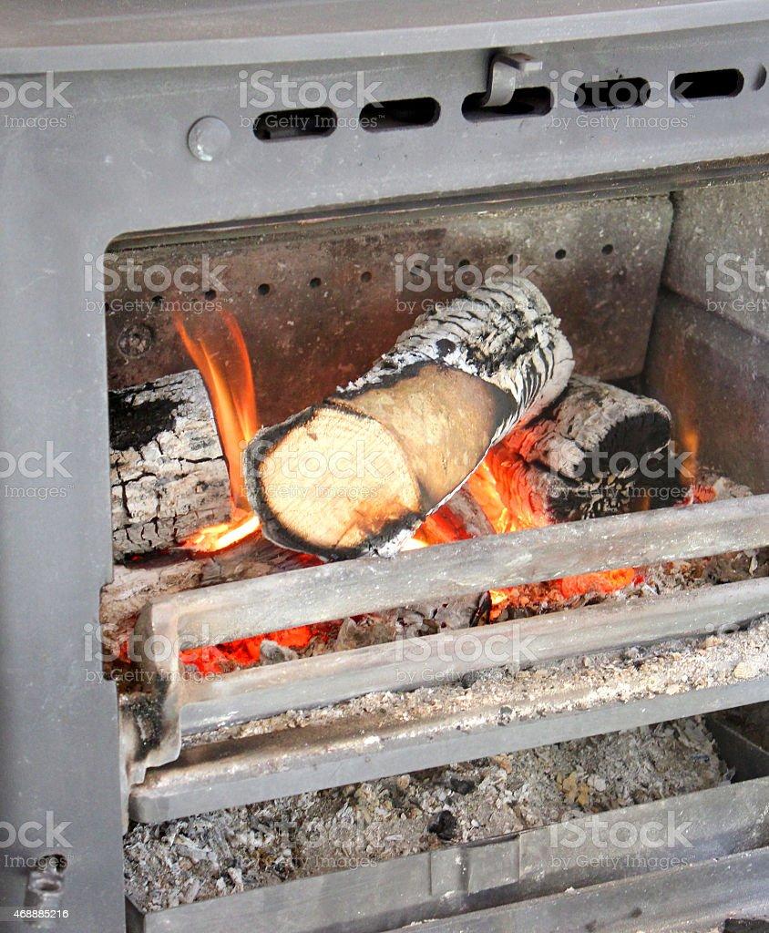 Image of wood-burning multi-fuel stove with burning logs, flames / fireplace stock photo
