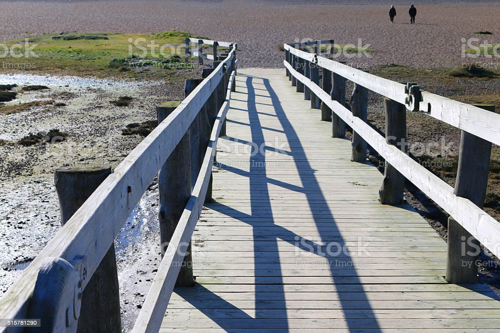 Image of wooden boardwalk crossing boggy ground to pebble beach stock photo
