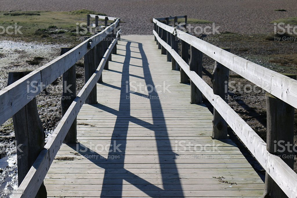 Image of wooden boardwalk crossing marshy ground to pebble beach stock photo