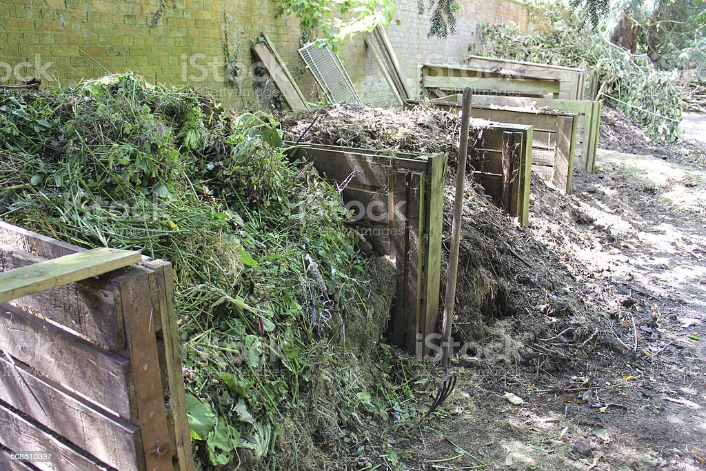 Image of wooden compost heaps, shady garden corner, recycling waste stock photo