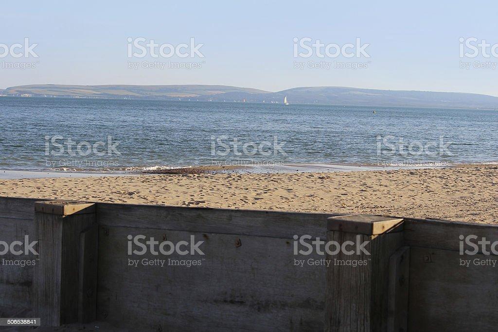 Image of wooden seaside groyne on sandy beach, sea defence stock photo