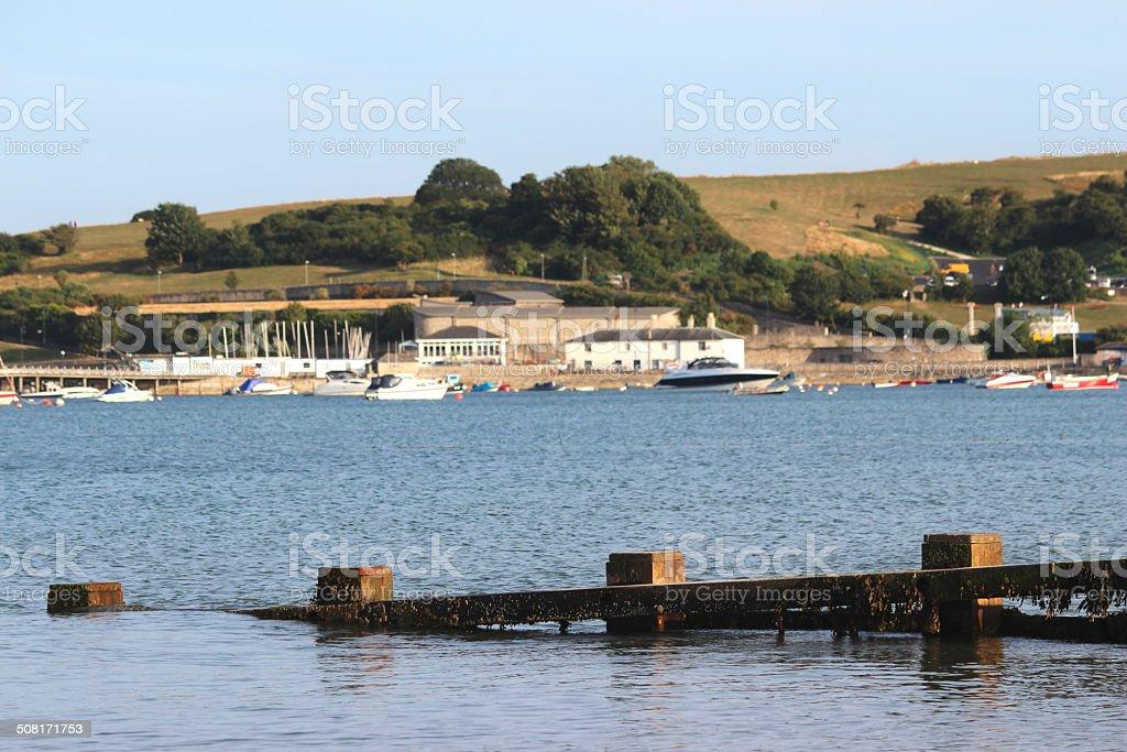 Image of wooden seaside groyne, sandy beach, sea-defence, town, yachts stock photo