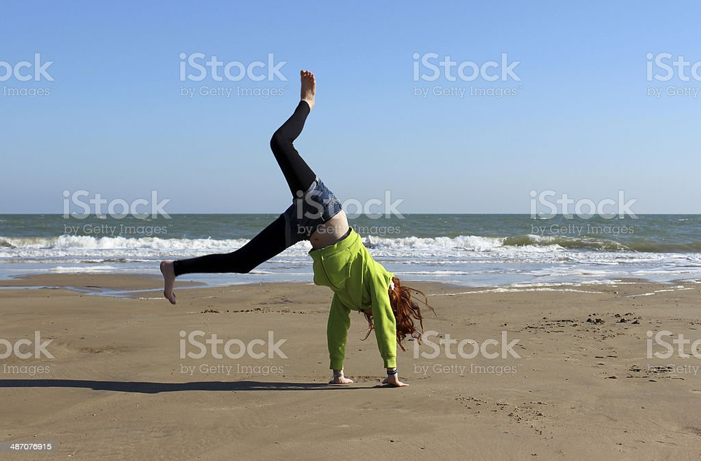 Image of young girl doing cartwheels and exercise on beach stock photo