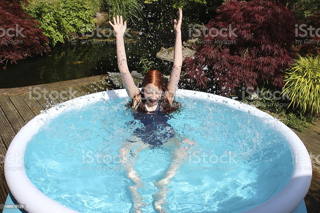 Image of young girl playing in inflatable paddling pool, splashing stock photo