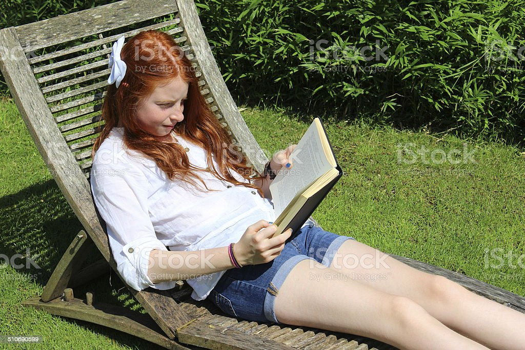 Image of young girl reading book, wooden garden sunlounger / steamer stock photo