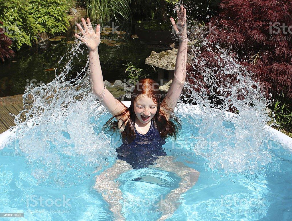 Image of young girl splashing in garden paddling pool, sunshine stock photo