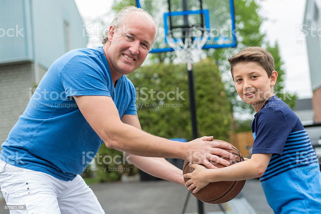 Image of young man and his son playing basketball stock photo