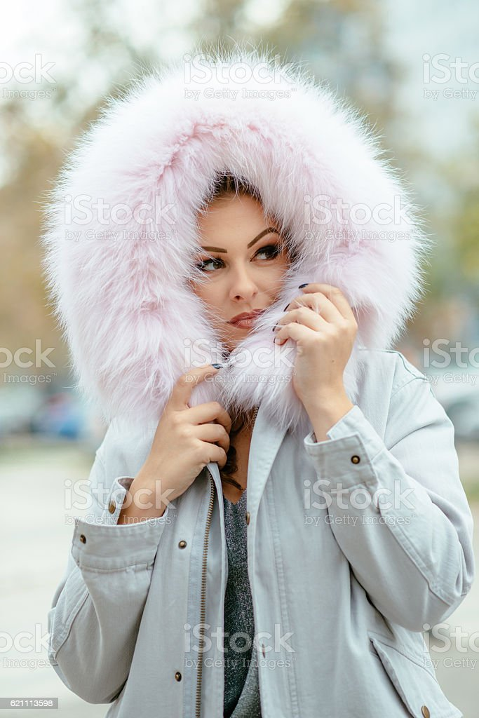 Image of young woman with hood with fur in winter stock photo