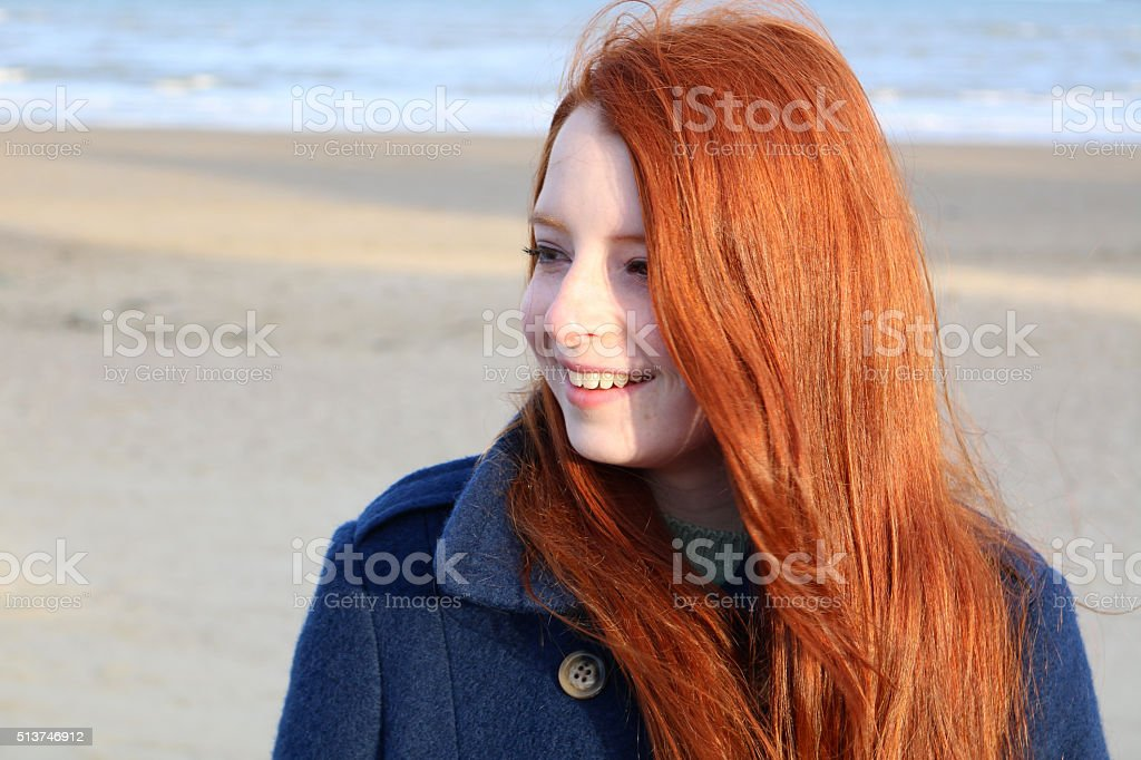 Image portrait of smiling red haired teenage girl, beach background stock photo