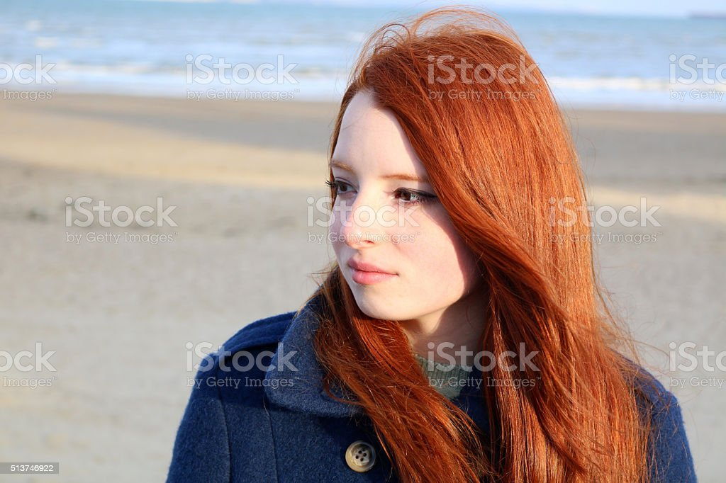 Image portrait of stunning red haired teenage girl, beach background stock photo
