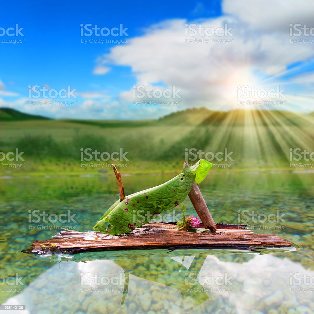 Imaginative little sail boat in a mountain lake stock photo