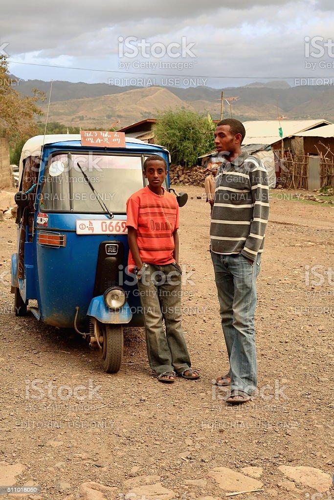 iMan and boy and autorick under stormy sky. Kombolcha-Ethiopia. 0092 stock photo