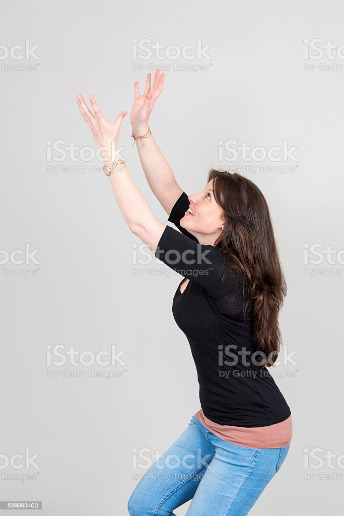 Imitation of young woman catching something out of the air stock photo