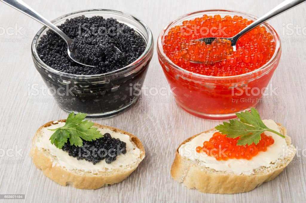 Imitation red and black caviar and spoons in bowls, sandwiches stock photo