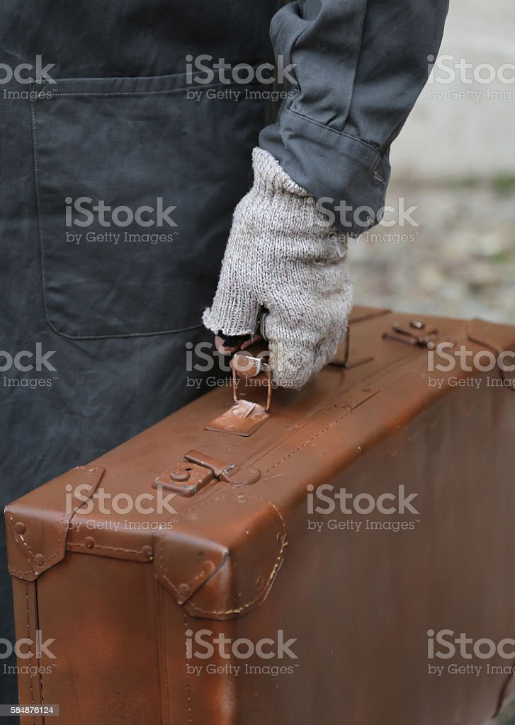 immigrant with old leather suitcase and broken gloves stock photo