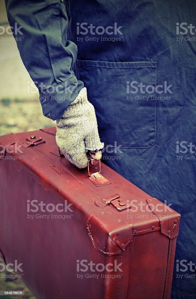 immigrant with old leather suitcase and the unstitched glove stock photo