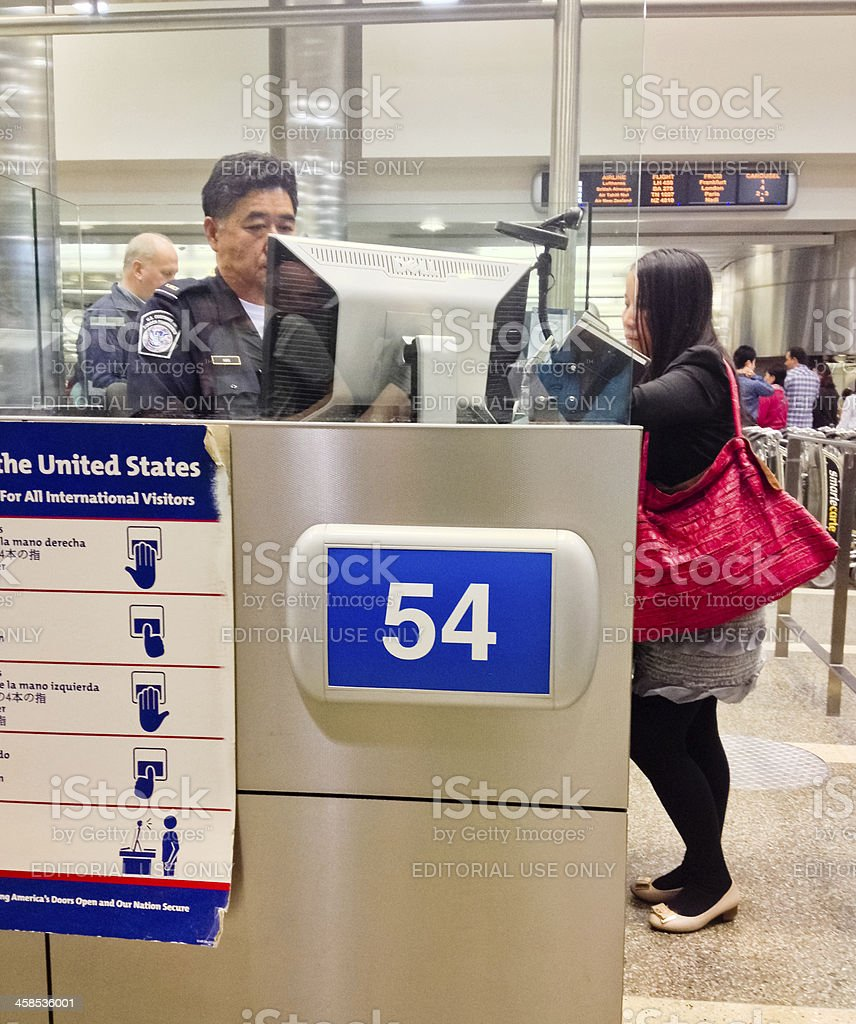 U.S. Immigration officer checking documents of tourists stock photo