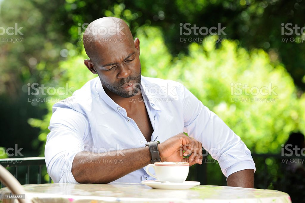 Impatient African man looking at watch royalty-free stock photo