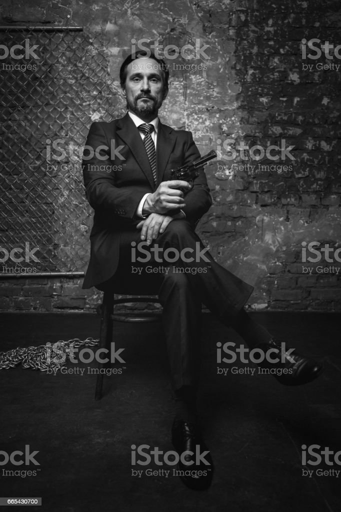 Imperious handsome crime leader making death treats stock photo
