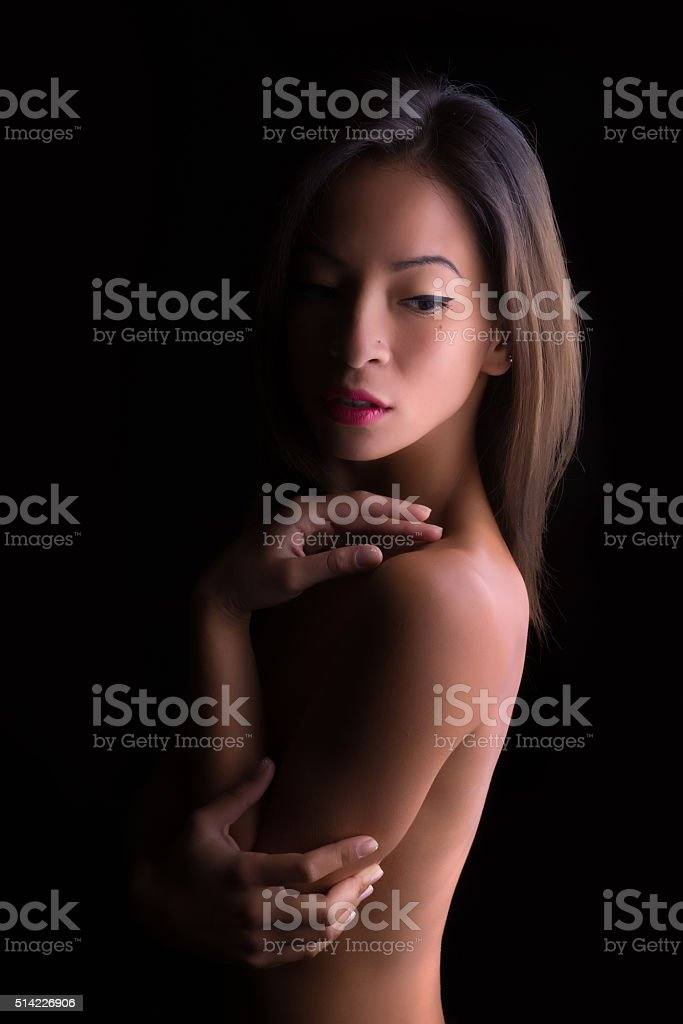 Implied nude in shadows stock photo