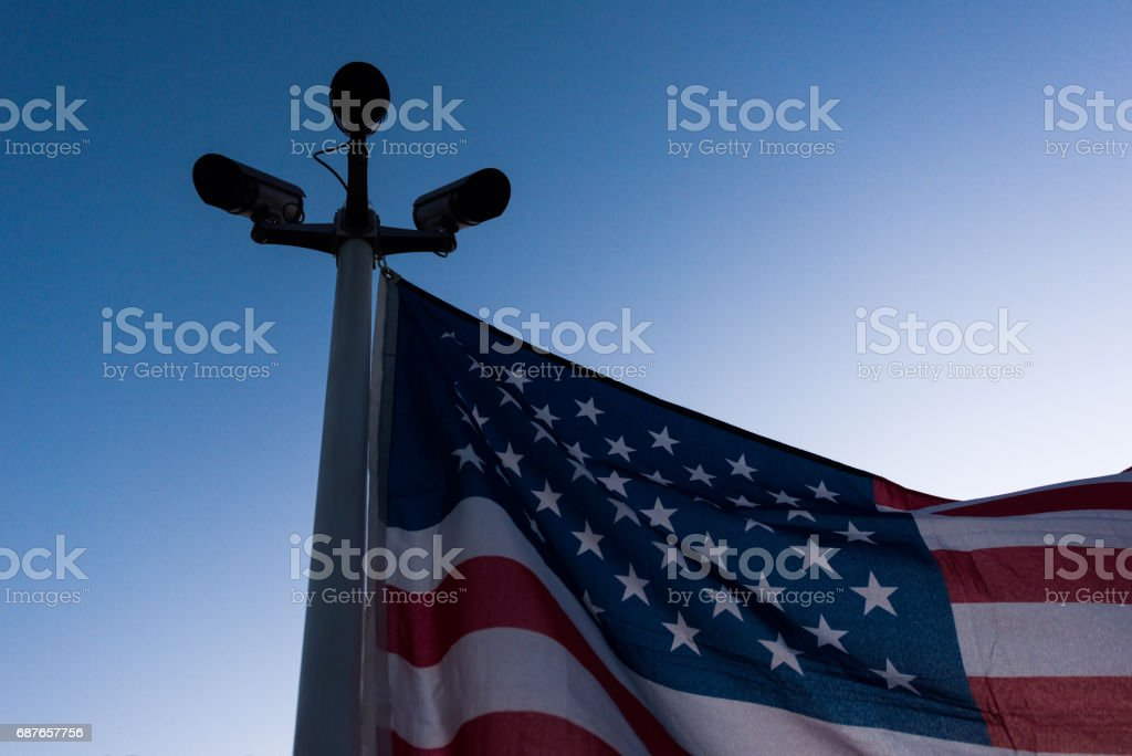 Imposing USA flag hanging on pole with three security cameras stock photo