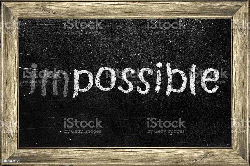 Impossible handwritten with white chalk on a blackboard. stock photo
