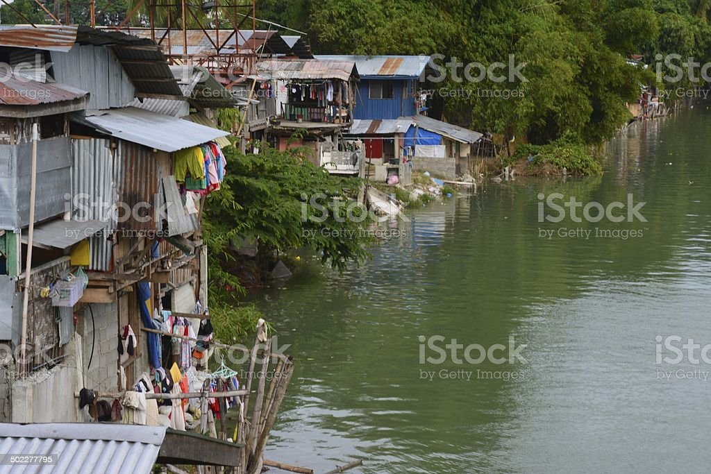 Impoverished houses situated on the river bank. stock photo