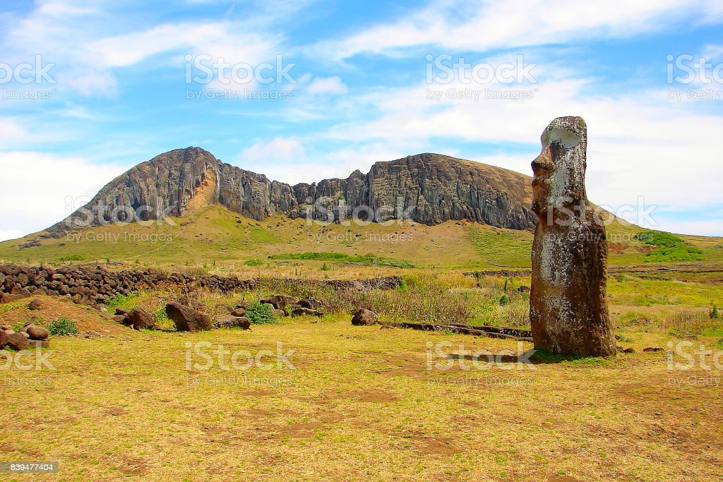 Impressive Easter Island - Rapa Nui ancient civilization -  lonely Moai statue in Idyllic countryside and Rano Raraku volcano - pacific ocean waves at coastline shore, dramatic landscape panorama – Chile stock photo