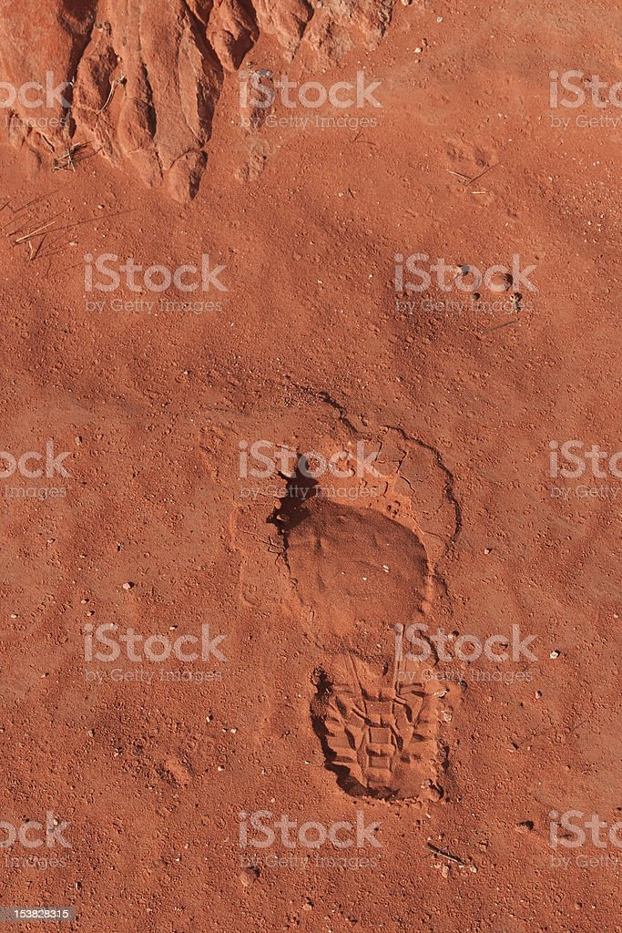 Imprint of the shoe on red stone sand royalty-free stock photo