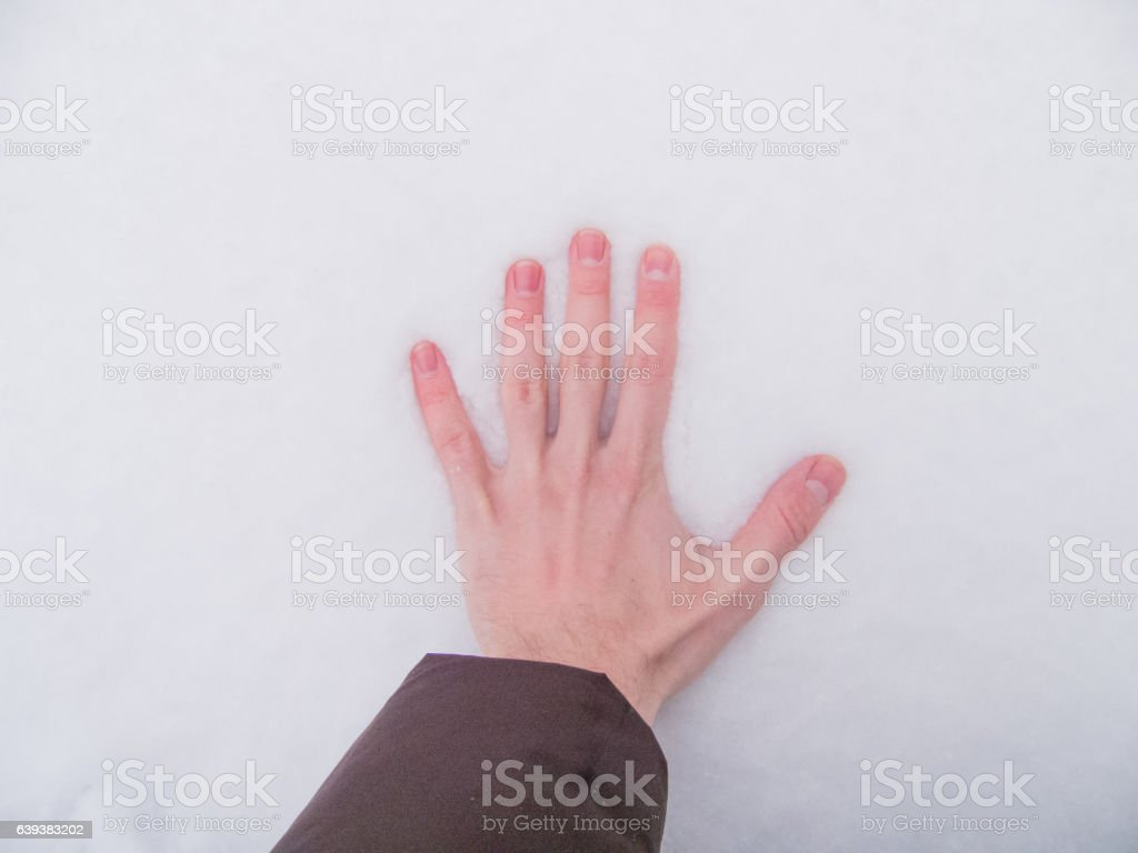 Imprinting a hand in the snow stock photo