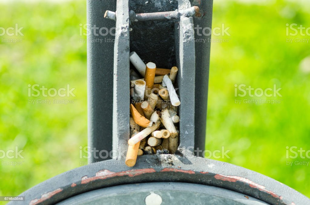 Improvised ashtrays on the street trashcan full of cigarette butts. Street ashtray. stock photo