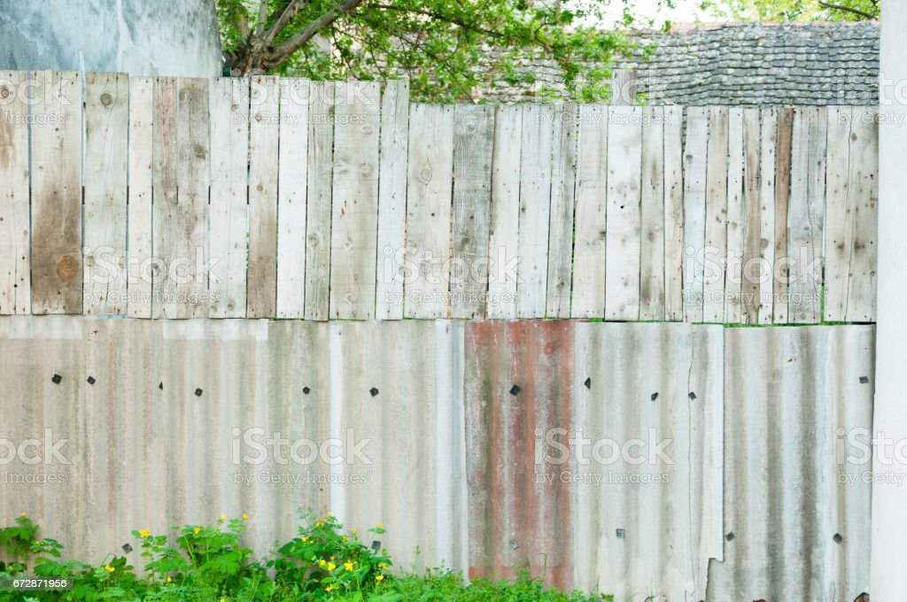 Improvised fence of wooden planks ceramic tiles for the roof. stock photo