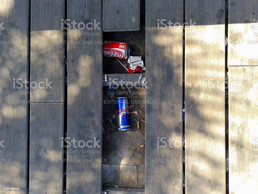 Improvised trash between public street floorboards stock photo