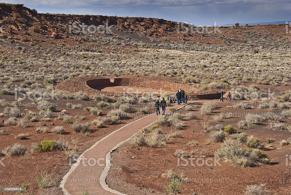 Visitors Walk to the Ball Court Near Wupatki Pueblo stock photo
