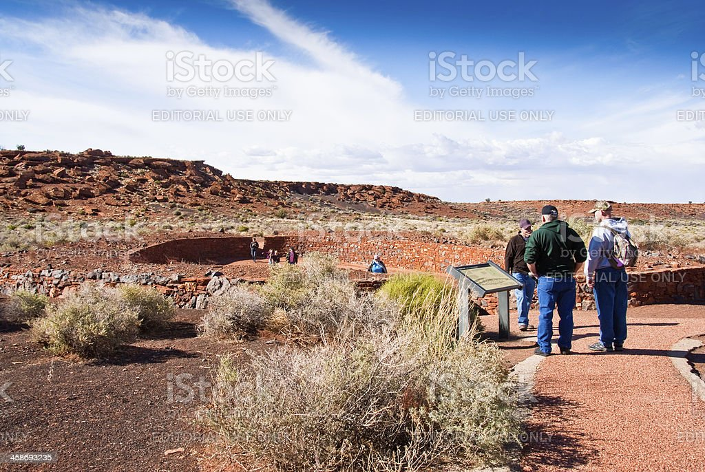 Visitors Look at the Ball Court Near Wupatki Pueblo stock photo