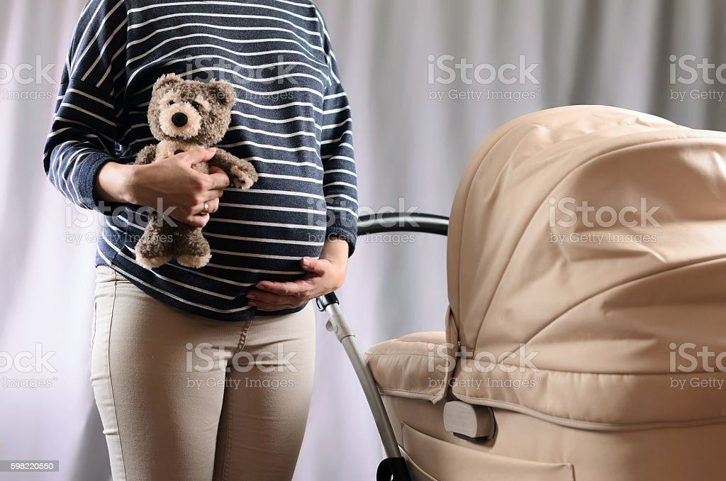 In anticipation of motherhood. Pregnant woman standing near a pr stock photo