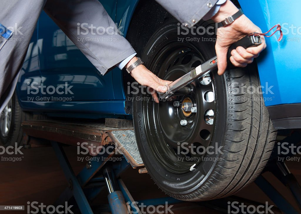In auto repair shop Car mechanic is changing tire royalty-free stock photo