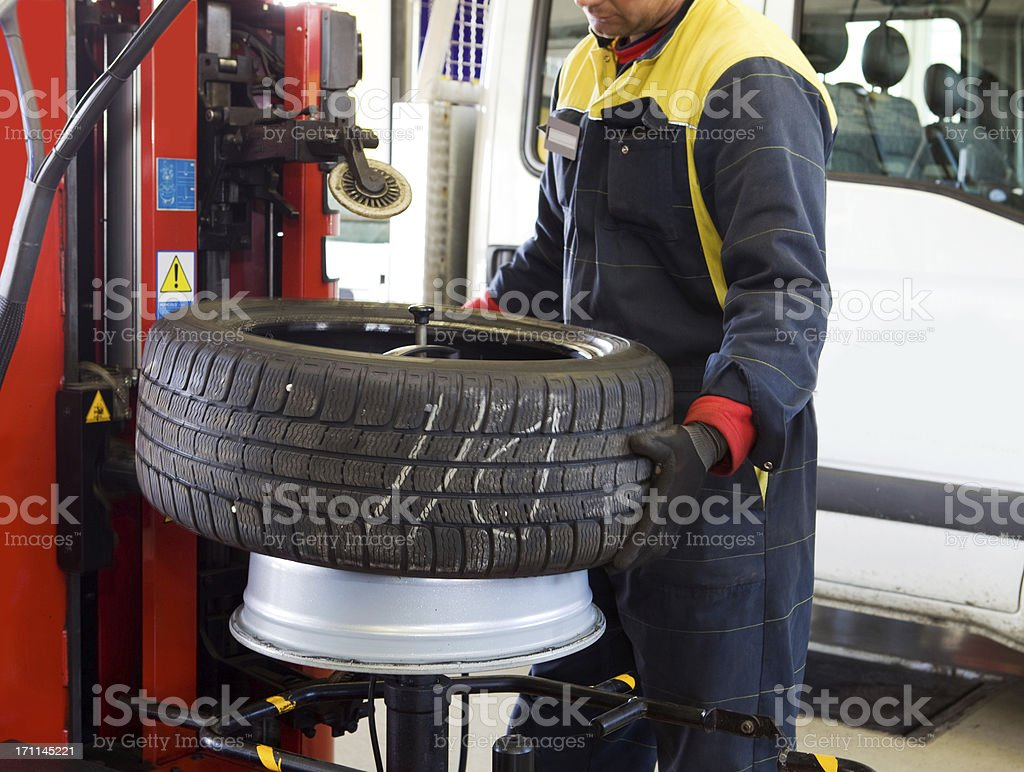 In auto repair shop....Auto mechanic is changin tire royalty-free stock photo
