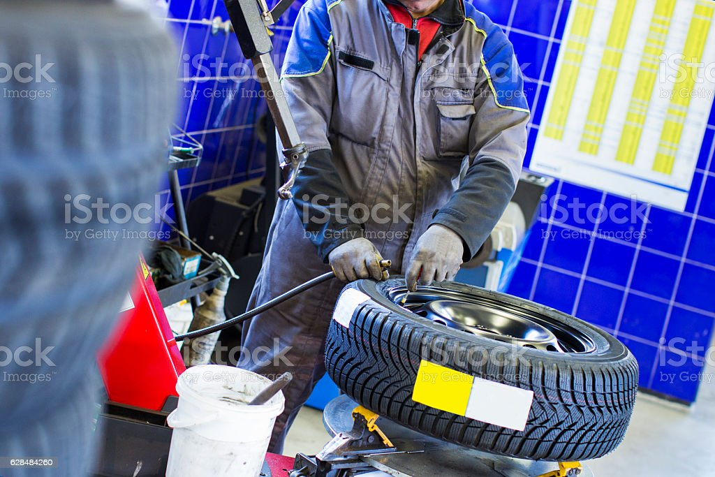 In auto repair shop...Car mechanic is  balancing winter tire stock photo
