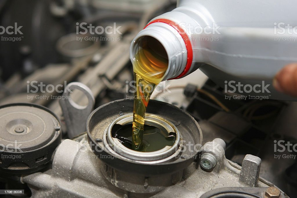 In auto repair shop...Car mechanic is changing engine oil stock photo