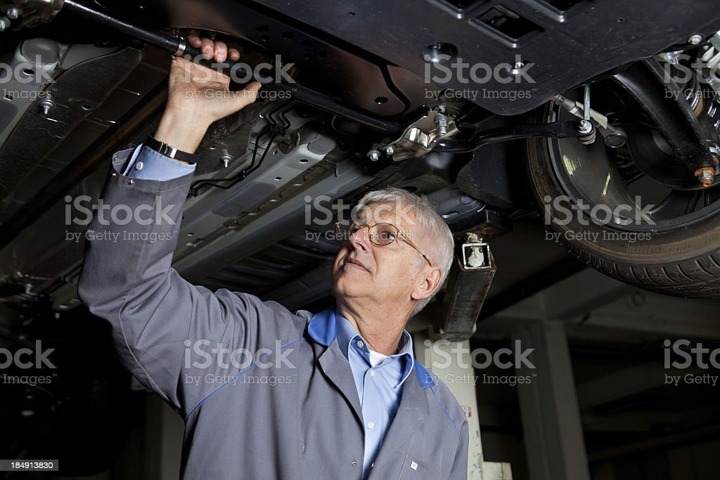 In auto repair shop...Car mechanic is checking chassis and suspension royalty-free stock photo