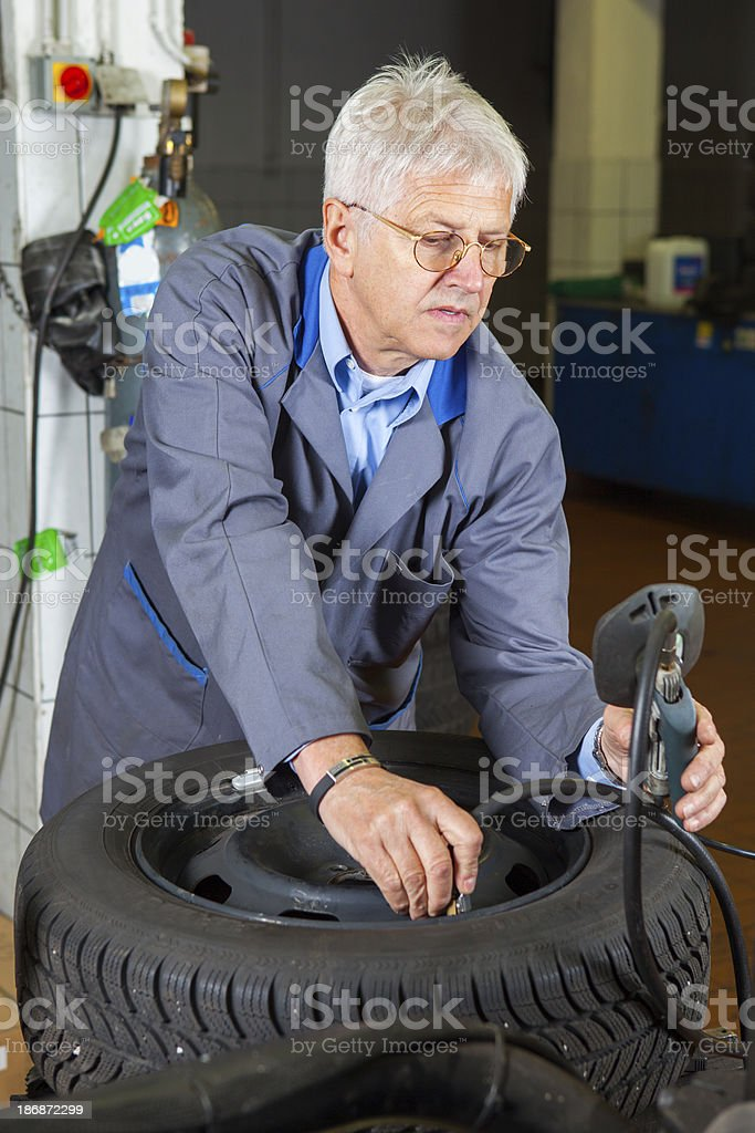 In auto repair shop...Car mechanic is checking tire air pressure royalty-free stock photo
