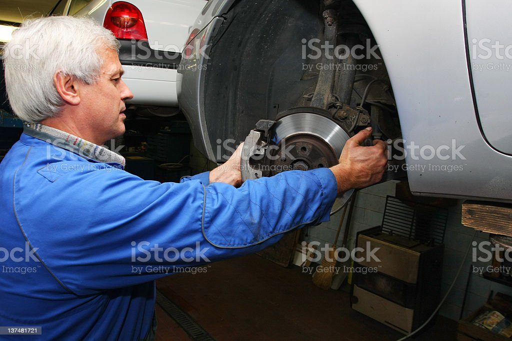 In auto repair shop...Car mechanic is fixing disc  brake royalty-free stock photo