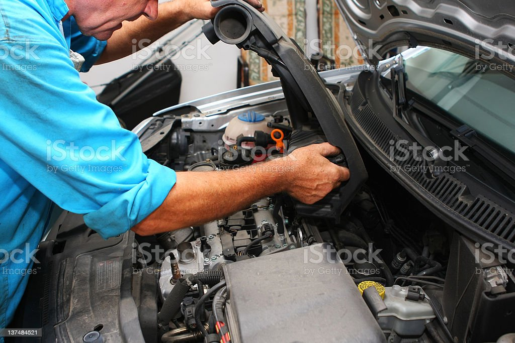 In auto repair shop....Car mechanic is fixing engine royalty-free stock photo
