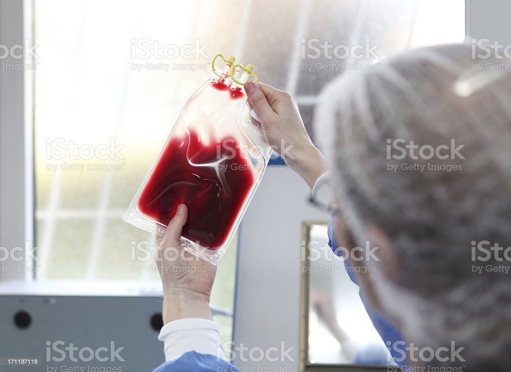 In  blood bank...Doctor in hazmat suit is checking blood bag royalty-free stock photo