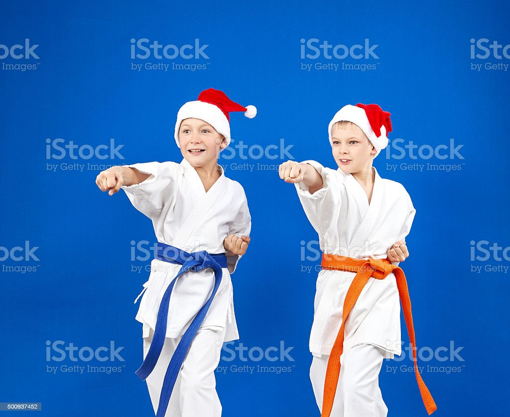 In caps of Santa Claus sportsmens are beating blows hands stock photo