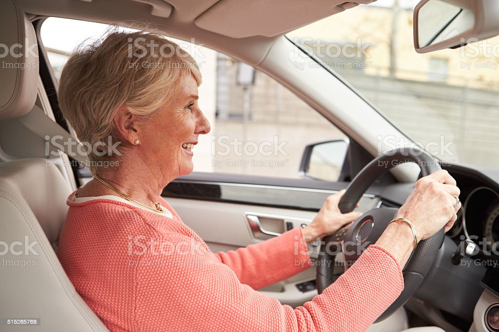 In car view of senior female driver at the wheel of stock photo
