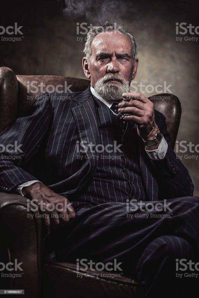 In chair sitting characteristic senior business man. Smoking cigar. stock photo